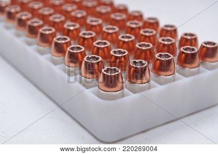 A plastic bullet container with .40 caliber hollow point bullets on a white background