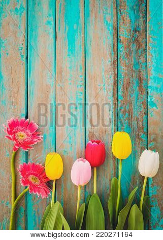 Colorful flowers on vintage wooden background, top view and border design. vintage color tone - flower of spring or summer background