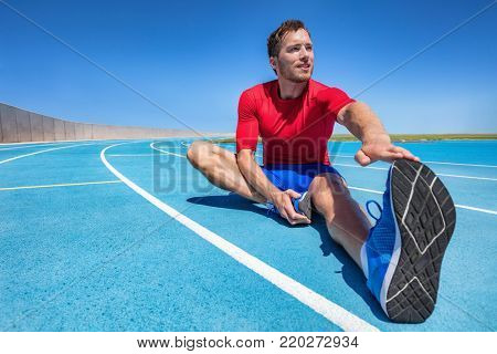 Man runner stretching legs preparing for run training on outdoor stadium running tracks Male fitness sport athlete outdoors doing warm-up toe touch single leg exercise.