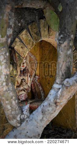 Balinese spiritual wooden statue with praying hands hidden in a niche