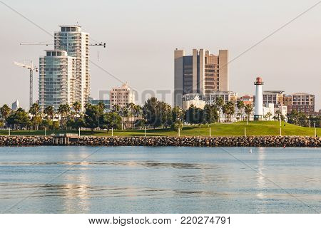 LONG BEACH, CALIFORNIA - SEPTEMBER 8, 2017:  Early morning light shines on the Shoreline Aquatic Park and the Rainbow Harbor Lighthouse on the shore of Long Beach harbor.