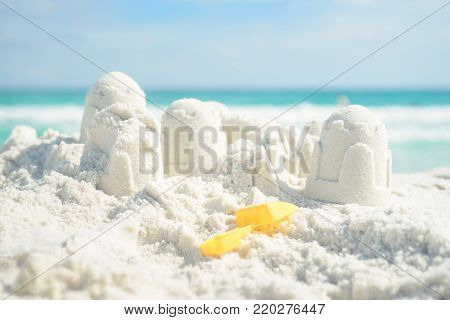 Sandcastle and yellow shovel on Florida beach with white sand, blurred ocean on background