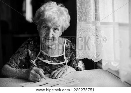 An elderly woman fills a receipt for payment of utility bills.