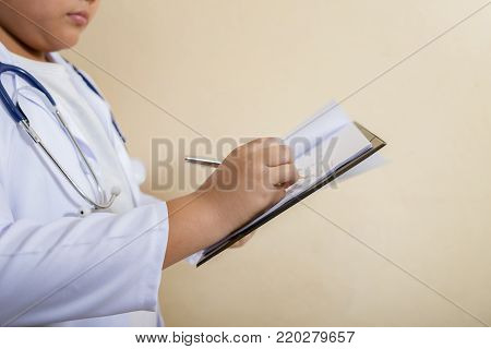Close-up of a man doctor filling out application form in the hospital.