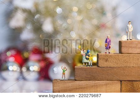 Miniature people with family holding balloon hang out in pine woods during winter.Selective focus.