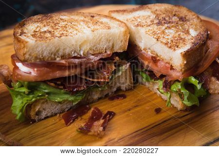 BLT sandwich with fried bacon, lettuce and tomato in slices of bread