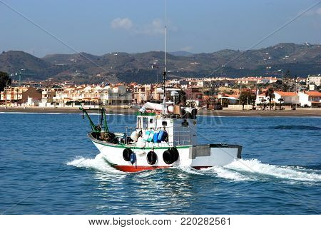 CALETA DE VELEZ, SPAIN - OCTOBER 27, 2008 - Traditional fishing boat leaving the harbour with buildings to the rear, Caleta de Velez, Malaga Province, Andalusia, Spain, Western Europe, October 27, 2008.