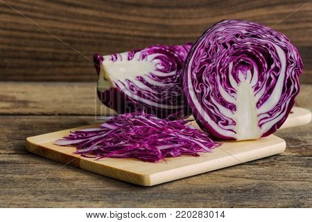 Chopped or sliced fresh purple cabbage on cutting board to shredded. Sliced purple cabbage with knife kitchen on wood table with copy space. Prepare vegetable for cooking cabbage salad or coleslaw. Homemade food concept of fresh purple cabbage.