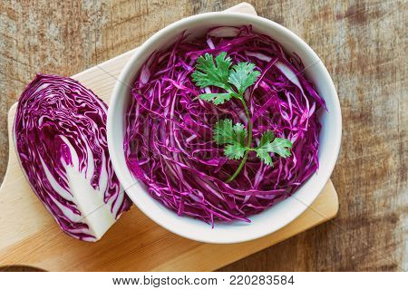 Cut or Sliced fresh purple cabbage in white bowl and decorate with coriander. Shredded cabbage in top view flat lay on wood table. Prepare vegetable for cooking cabbage salad or coleslaw. Homemade food concept. Sliced purple cabbage ready to cook.