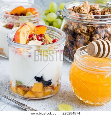 Granola with yogurt, berry and fruits in jar. Healthy yogurt granola parfait. Concept of healthy eating, healthy lifestyle and healthy snack. Closeup view, square crop