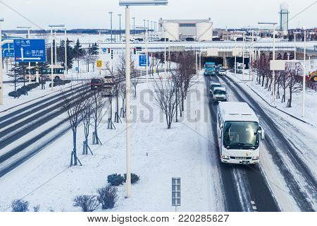 Hokkaido, Japan - 27 December 2017 - Vehicals travel on road at Chitose International Airport coverred with snow during winter in Hokkaido, Japan on December 27, 2017