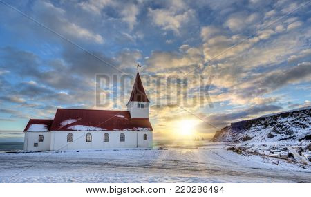 Typical red colored wooden church in Vik town, Iceland in winter. Sunrise light