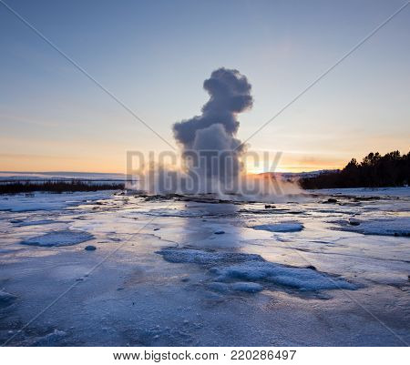 Eruption of famous Strokkur geyser in Iceland. Winter sunset.