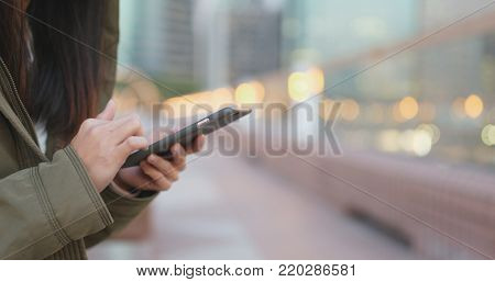 Close up of woman use of smart phone in the evening at winter time, woman wearing winter jacket at outdoor