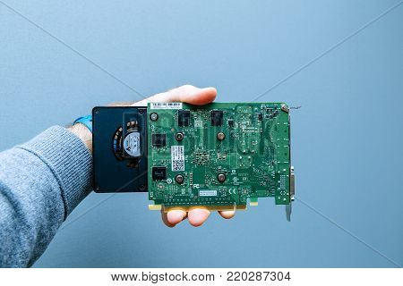 PARIS, FRANCE - NOV 6, 2017: Man holding against gray background powerful NVIDIA GPU video card from the Quadro line used in professional video production in bitcoin cryptocurrency mining