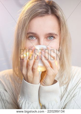 Adult woman drinks coffee. Female drinks hot drink in winter