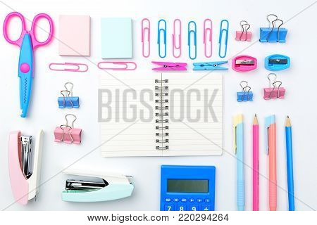 Stationary concept, Flat Lay top view Photo of Scissors, pencils, paper clips, sticky note,staple with blank note pad in pink and blue tone on white background with copy space.