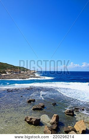 View along the coastline with rocks in shallow water in the foreground, Redoubt, Marsalforn, Gozo, Malta, Europe.
