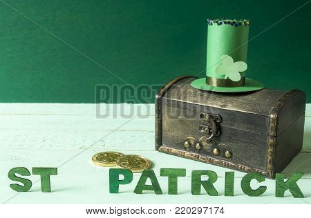 St Patrick words and hat on a treasure chest - Saint Patrick written in green wooden letters, a tall hat, specific for St Patrick holiday, on top of an old treasure coffer with gold coins near it.