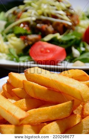 Crispy chunky chips with mixed salad topped with roast vegetables to the rear on a wooden table within the citadel, Victoria (Rabat), Gozo, Malta, Europe.