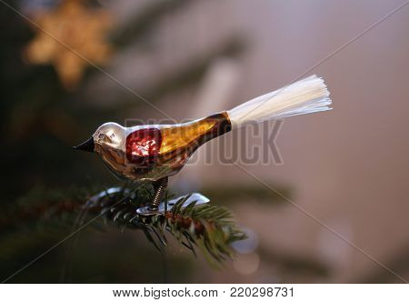 cute Christmas decoration in the shape of a colorful bird on the twig of a tree