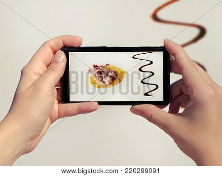 Female take picture of high quality food in a restaurant on white background on mobile phone. High quality cooking like octopus in yellow garlic sauce. High quality food on smart phone. Luxury food isolated