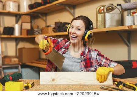 Pretty caucasian young brown-hair woman in plaid shirt, gray T-shirt, noise insulated headphones, yellow gloves working in carpentry workshop at wooden table place with different tools, sawing wood
