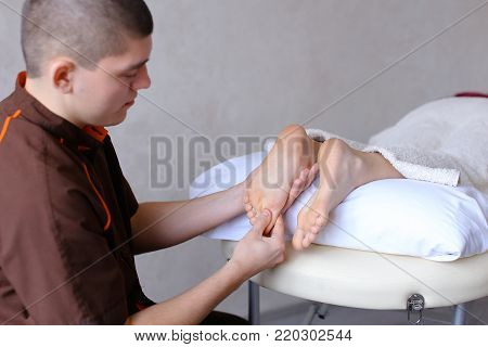 Sociable and professional man doctor actively rubs feet and conducts medical procedure, talking with female patient who lies on couch in light cosmetic salon. Man of European appearance with short haircut dressed in brown medical uniform