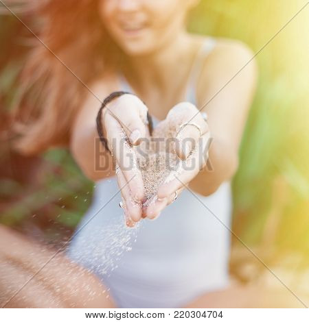 Cheerful woman sits in lotus pose and keeps sand in hands. Daily sun shines brightly, female smiles nice and happily. Sand stones freely flow through thin fingers and fall down. Square picture