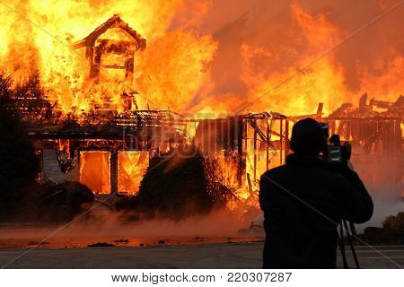 A photographer snaps a photo of a house fire that has totally engulfed a home in flames.