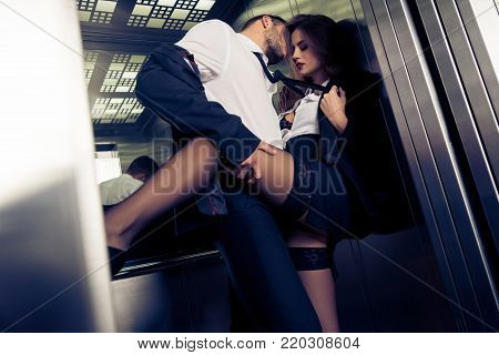 view of sensual attractive business couple in elevator