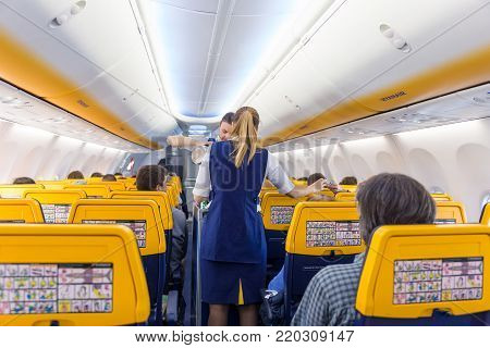 Valencia, Spain - Dec 14, 2017: Interior view of stewardess serving passangers on Ryanair low-cost flight on 14th of December, 2017 on a flight from Trieste to Valencia.