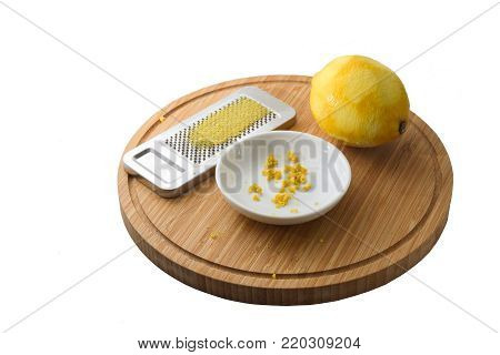 organic lemon fruit, freshly grated peel or rind and the grater on a wooden cutting board, isolated on a white background with copy space, selected focus, narrow depth of field