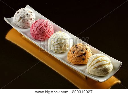 Ice cream scoops of different colors and flavours with chocolate and strawberry