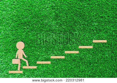 Walking man carry a bag up the stairs walks up to the goal to succeed paper cut of a green background