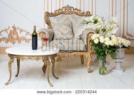 Luxurious vintage interior in the aristocratic style with elegant armchair and flowers. Bottle and glass of wine on the table. Retro, classics