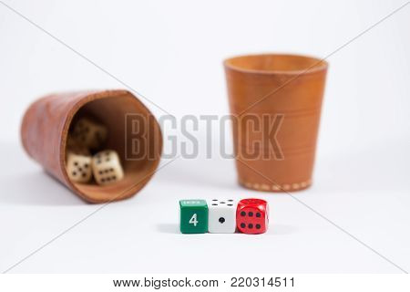 two brown leather cups filled with dice and three white red green colored dice showing four one six isolated on white background shallow depth of field