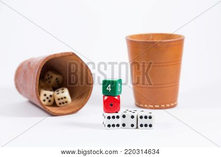 two brown leather cups filled with dice and five white red green colored dice stacked on top of each other showing four one six four six isolated on white background