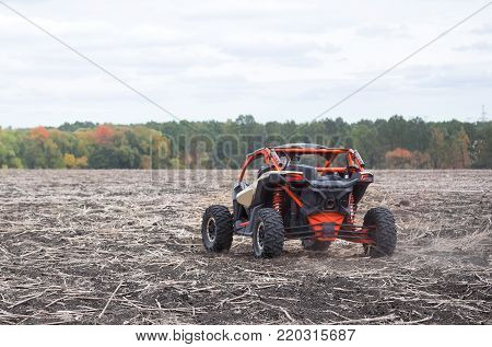 Quad bike of red color shot from behind. Red buggy in plowed field against the background of autumn trees. concept of power speed and freedom.
