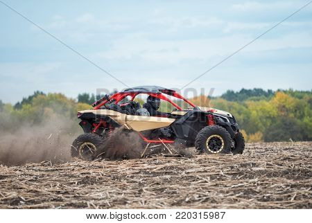 Red buggy with two people in helmets on plowed field in the dust. The concept of speed of power and freedom.