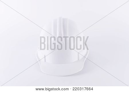 White safety helmet on white background. Hard hat and thick gloves on white isolated background. Safety equipment concept. Worker and Industrial theme.