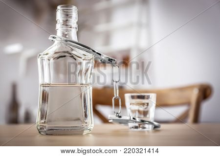 Bottle and glass of alcohol with handcuffs on wooden table. Concept of alcohol dependence