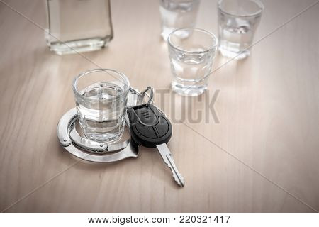 Glass of alcohol with handcuffs and car key on wooden table. Don't drink and drive concept