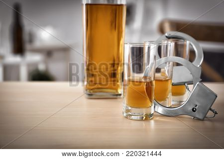 Glassware of alcohol with handcuffs on wooden table. Concept of alcohol dependence