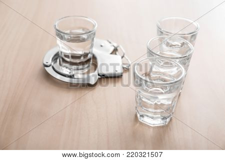 Glasses of alcohol with handcuffs on wooden table. Concept of alcohol dependence