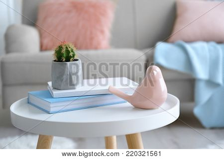Houseplant with stack of books and ceramic bird on table in living room
