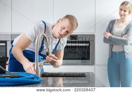 Smiling housewife watching a plumber repairing a faucet in the kitchen