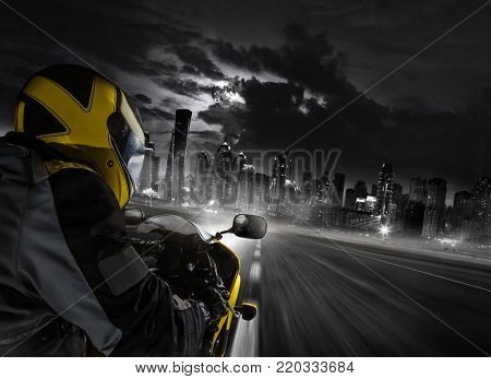Detail of super-sport motorbike rider heading to the modern city. Concept of speed, travel and freedom. Dubai skyscrapers on background