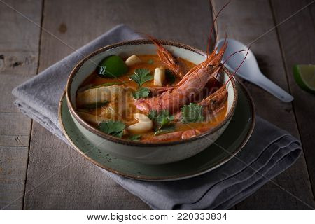 Traditional Thai soup Tom Yam prepared with shrimps, calamari and herbs