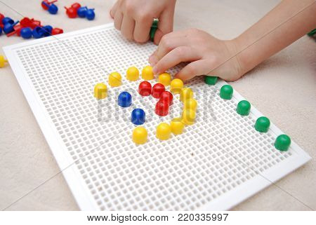 Childrens hands playing with mozaic creative game